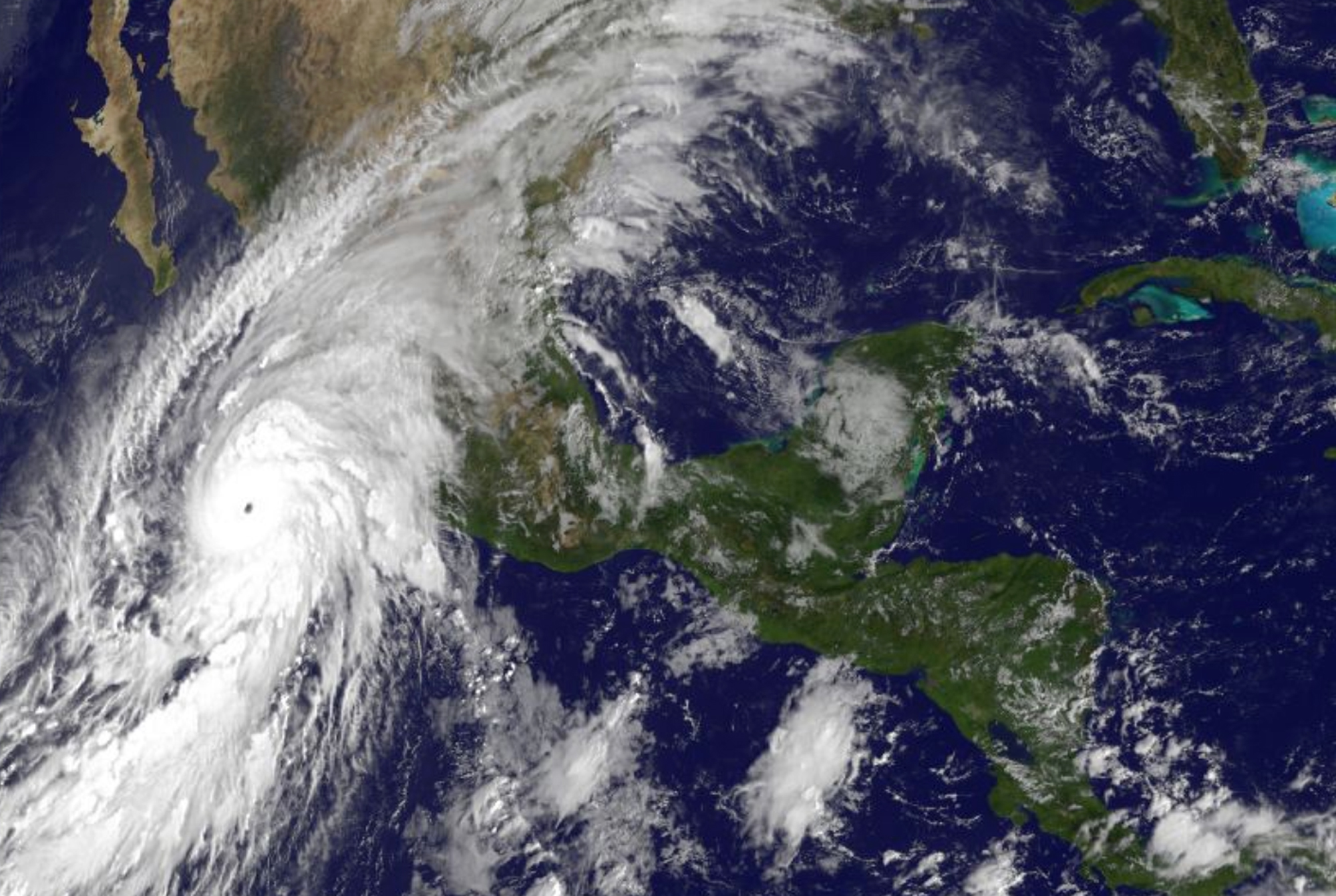 """CORRECTS TIME TAKEN TO 10 A.M. NOT 11 A.M. - This satellite image taken at 10 a.m.. EDT on Friday, Oct. 23, 2015, and released by the National Oceanic and Atmospheric Administration shows Hurricane Patricia, left, moving over Mexico's  Pacific Coast. Hurricane Patricia headed toward southwestern Mexico Friday as a monster Category 5 storm, the strongest ever in the Western Hemisphere that forecasters said could make a """"potentially catastrophic landfall"""" later in the day.  (NOAA via AP)"""