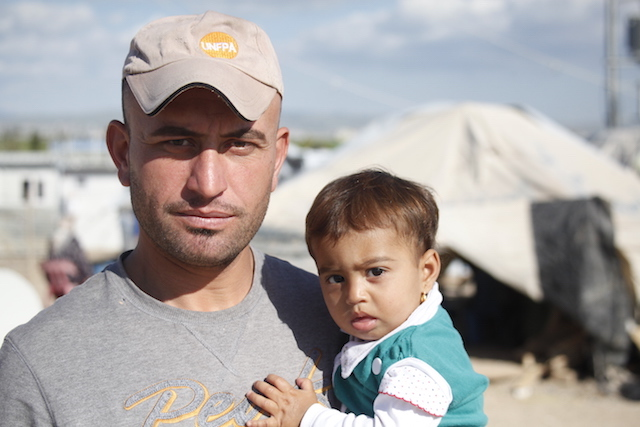 Man and child in refugee camp
