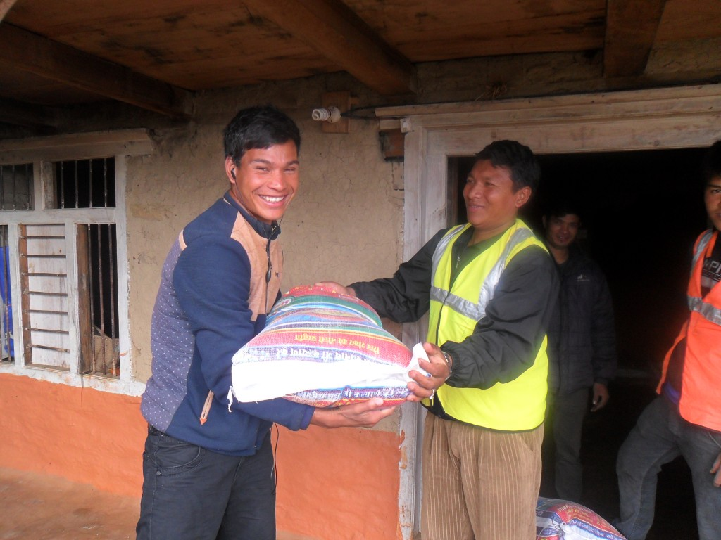 Patrush Shrestha (one of our evangelists from Sailung) distributing rice to his villagers