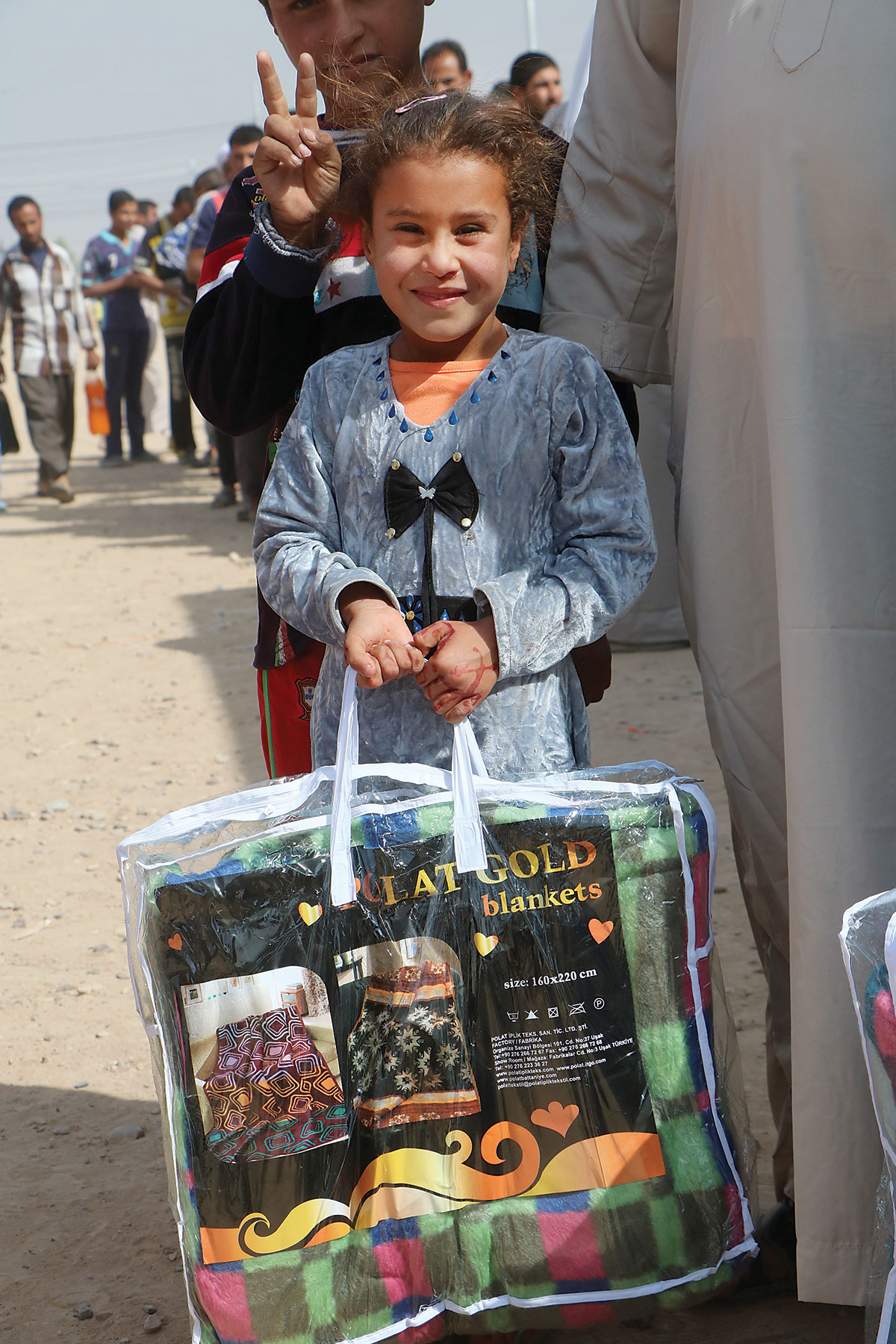 Refugee-child-with-aid-supplies