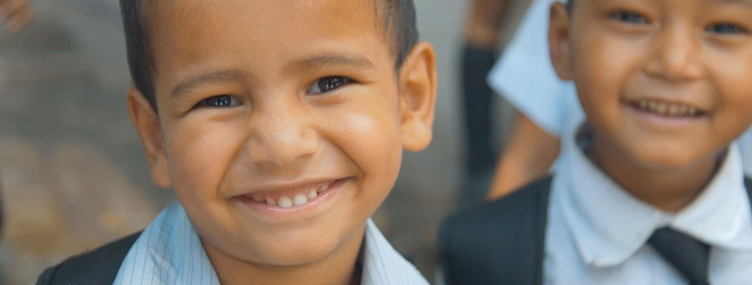 Young boy in a school uniform smiling at the camera.
